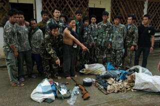 Park rangers stand with arrested poachers (in bare feet) who point to  seized illegal wildlife parts, weapons, and other equipment in Thailand's Western...
