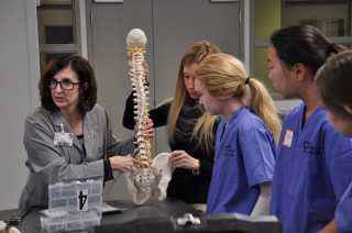 Terri Cappello, MD, instructs high school girls to perform mock surgery.