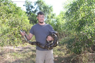 J.D. Willson, an assistant professor at the University of Arkansas, holds a Burmese python during fieldwork in the Florida Everglades