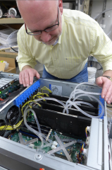 Timothy Shedd examines a computer equipped with his novel cooling system. Tubes circulate refrigerating fluid through a special heat exchanger (under the X-shaped...