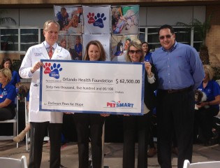 PetSmart presents a check for $62,500 to the PetSmart Paws for Hope at Orlando Health pet therapy program. From left to right, Dr. Mark Roh, President,...