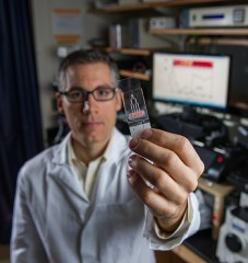 Craig Forest, an assistant professor of bioengineering in the George W. Woodruff School of Mechanical Engineering at Georgia Tech, holds the microfluidic...