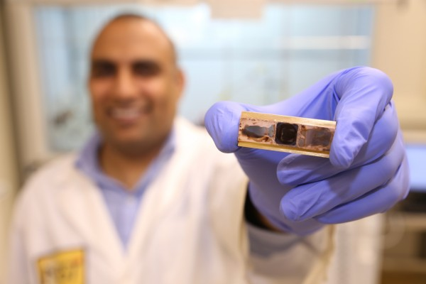 Research scientist Virendra Singh, from the George W. Woodruff School of Mechanical Engineering at Georgia Tech, holds a test sample used to measure thermal conductance and thermal cycle reliability in a new polymer material developed to remove heat from electronic devices.