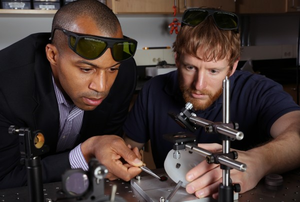 Assistant professor Baratunde Cola, from the George W. Woodruff School of Mechanical Engineering at Georgia Tech, and Ph.D. student Tom Bougher, show photoacoustic test equipment used to measure heat conductance of a new polymer material developed for thermal management.