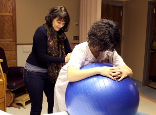 Expectant mom Katy VanderWal, right, of rural Brookings, uses a birthing ball during labor with the help of her doula, Taylor Mertz. VanderWal gave birth...