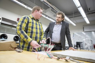 "Konstantin Sobolev (right) consults with doctoral student Scott Muzenski while the two look at a sample of a ""smart"" concrete composite they developed..."