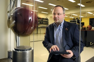 Stefan Duma, the department head of biomedical engineering at Virginia Tech, demonstrates a helmet-impact test conducted in laboratory conditions. Testing...