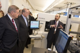 Prof. Jay Tischfield (far right) explains one of the new systems RUCDR has installed to Sen. Robert Menendez (far left) and Rutgers President Robert Barchi.