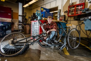 A Michigan Tech Senior Design student works on a handcycle for the Achilles Freedom Team  of wounded veterans.