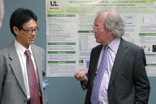 John Codey (right) of the Helmsley Charitable Trust discusses with Dr. Nobuyuki Matoba his work into finding a vaccine to prevent cholera, which in turn...