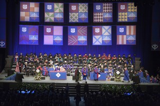 Students process across stage at the combined ceremony of the 2012 commencement of the College of Liberal Arts and Social Sciences, and the College of Science...
