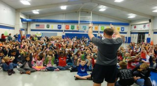 Dorsett Shoals Elementary School physical education teacher Nick Epstein addresses students at an assembly to encourage good hand hygiene habits.
