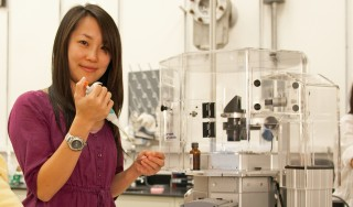 University of Utah physics doctoral student Pei-I Ku prepares a sample for the digital microscope she uses to make movies and photographs of the AIDS-causing...