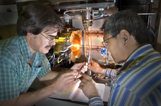 Scientists in front of a furnace for growing perfect crystals of superconductors at Brookhaven National Laboratory.