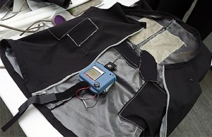 The conductive textile cloth for the shocking electrodes is sewn into the back of the prototype vest, where the two light gray rectangles can be seen.