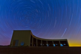 In this time-lapse photo, stars appear to rotate above the Middle Drum facility of the Telescope Array, a $25 million cosmic ray observatory that sprawls...