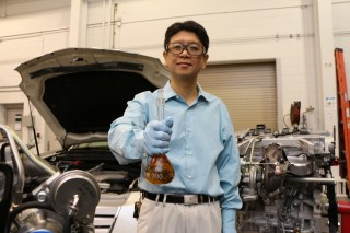 Jun Qu displays a flask of the Ionic Liquid Anti-wear Additives for Fuel-efficient Engine Lubricants, one of ORNL's eight 2104 R&D 100 Award winners.