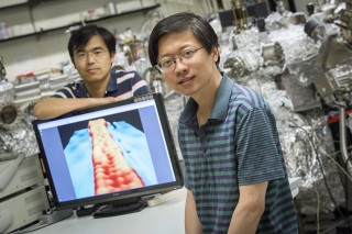 Yaoyi Li (foreground) and Mingxing Chen, UWM physics postdoctoral researchers, display an image of a ribbon of graphene 1 nanometer wide. In the image,...