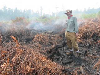 Smoke in the background provides evident that thin layers of the organic matter compacted beneath senior scientist Mark Cochrane's feet are on fire....