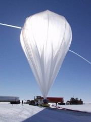 High-pressure helium from Kelly trucks carrying gas cylinders rushes through fill tubes extending from the top of a balloon that is pinned to the ground...