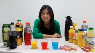 University of Adelaide School of Dentistry Honors student Chelsea Mann with a selection of acidic drinks and sweets that can cause permanent damage to teeth.
