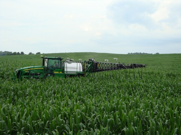 A large sprayer applies nitrogen fertilizer to a field. The equipment is assisted by technology that optimizes the application of fertilizer—using it only where needed on the field. This reduces cost to the grower.