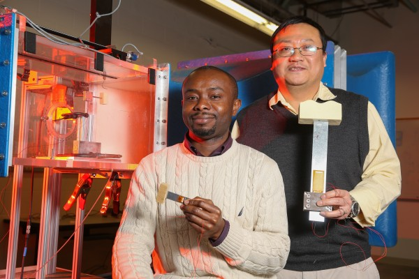 Felix Ewere, left, and Dr. Gang Wang near a wind tunnel they use for testing in UAH's Olin B. King Technology Hall. Inside the tunnel is their latest miniaturization effort, while Ewere holds the intermediate effort and Dr. Wang holds the initial device constructed.