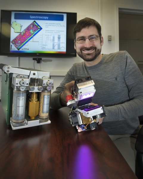 Shawn Serbin, broadly trained in forest ecology, plant physiology, ecosystem science and remote sensing, is holding an infrared gas analyzer used to measure photosynthesis.