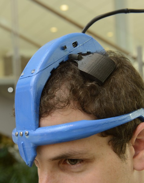 One of the Johns Hopkins student inventors demonstrates how the noninvasive brain stimulation prototype would fit on a Parkinson's patient's head.