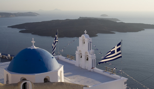 Greece's flag flies in Santorini. DePaul University faculty experts are available to provide insight and commentary on the financial and political crisis in Greece.