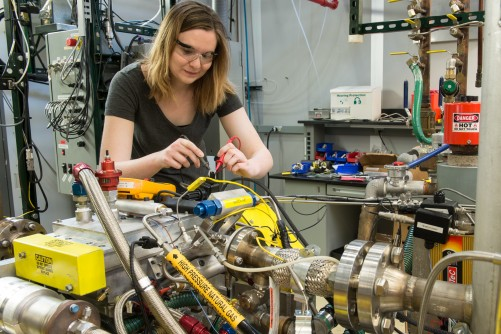 Visiting IIT Professor Carrie Hall troubleshoots the engine wiring harness. The system can replicate speed and load conditions found during typical vehicle operation for both naturally aspirated as well as turbocharged engines.