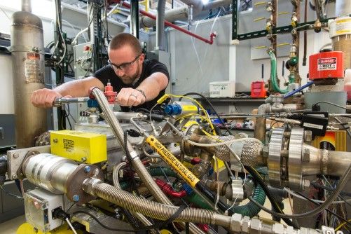 Argonne researcher Jim Sevik tightens the fuel rail on a natural gas direct-injection system at the lab. The engine is an automotive size single-cylinder research engine that operates with gasoline as well as natural gas.