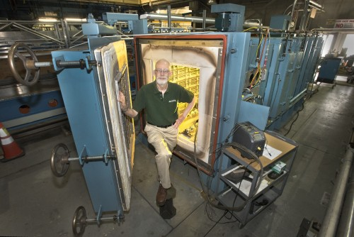 Brookhaven physicist Peter Wanderer, head of the laboratory's Superconducting Magnet Division, stands in front of the oven in which niobium tin is made into a superconductor.