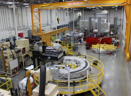 A partial view of the General Atomics module fabrication line, with two winding station tables visible behind a yellow rail.
