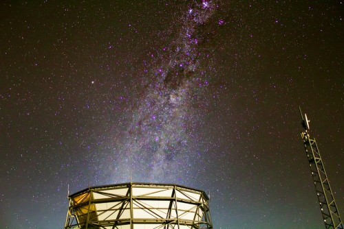 The Milky Way's galactic plane rises above the Atacama Cosmology Telescope. The Simons Observatory is planned at the same site and will merge existing experiments and add new telescopes and detectors.