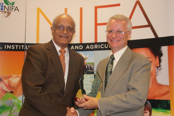 PINEMAP principal investigator Tim Martin, right, accepts congratulations from Sonny Ramaswamy, director of the USDA's National Institute of Food and Agriculture, at the NIFA Partnership Awards ceremony in Washington, D.C., on Thursday, Oct. 6, 2016.