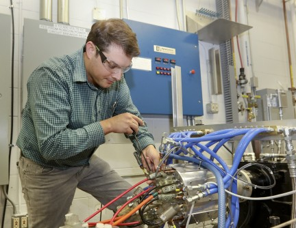 Oak Ridge National Laboratory researcher Tim Burress works with a prototype motor that generates 75 percent more power than comparable commercial motors without the use of rare earth materials.