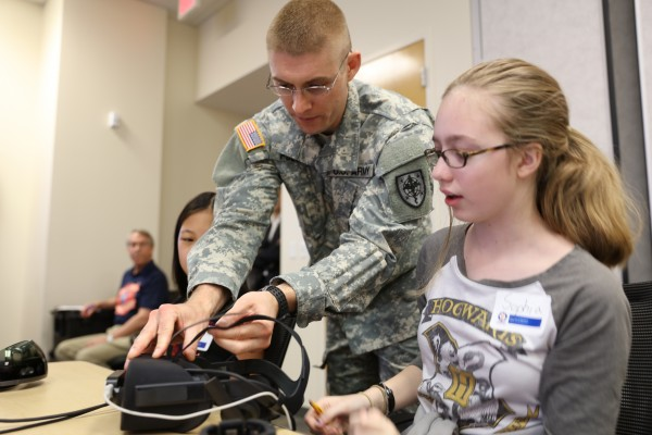 Army 2nd Lt. Michael Polmear, a medical student at the Uniformed Services University of the Health Sciences, helps an attendee at the JHU APL CONVEY STEM Workshop with her virtual reality headset.