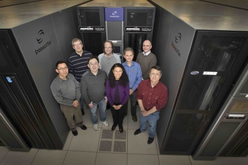 (Back row) Ognian Novakov, Christopher Pinkenburg, Jérôme Lauret, Eric Lançon, (front row) Tim Chou, David Yu, Guangwei Che, and Shigeki Misawa at Brookhaven Lab's Scientific Data and Computing Center, which houses the Oracle StorageTek tape storage system where experimental data are recorded.