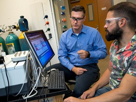 Professor Daniel Shantz (left) and graduate student Ross Ransom analyze data from their research of zeolite SSZ-39 in an effort to reduce harmful chemicals in auto emissions.