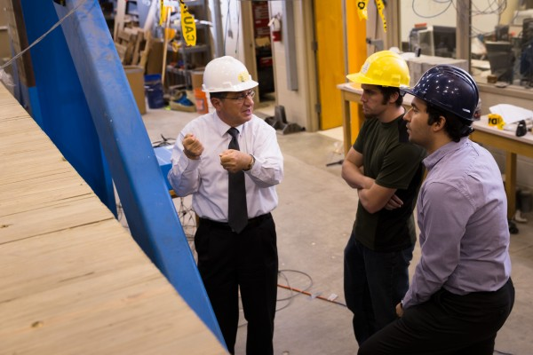 Professor Nadim Wehbe, graduate student Zachary Carnahan and assistant professor Mostafa Tazarv discuss progress on testing the timber girder bridge.