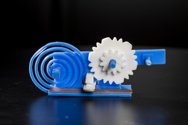 The 3-D printed gears (in white) and spring (blue spiral) toggle a switch (white box with grey surface) made of conductive plastic. The switch changes the reflective state of a 3-D printed antenna (gray strip) to convey useful data to a WiFi receiver. The shape of the gears and the speed at which they move encode the digital data.