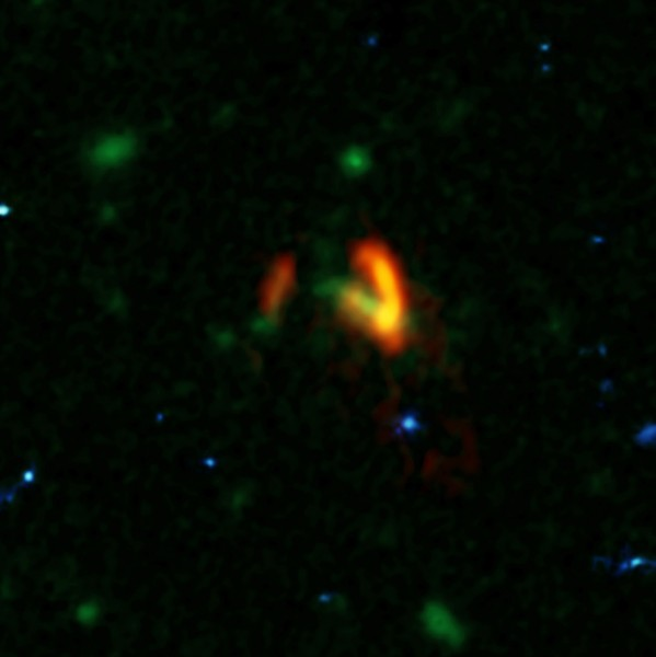 A composite image showing ALMA data (red) of the two galaxies of SPT0311-58. These galaxies are shown over a background from the Hubble Space Telescope (blue and green). The ALMA data show the two galaxies' dusty glow. The image of the galaxy on the right is distorted by gravitational lensing. The nearer foreground lensing galaxy is the green object between the two galaxies imaged by ALMA.