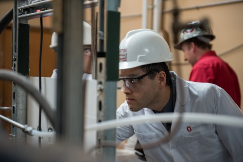 Andrew Tong, research assistant professor of chemical and biomolecular engineering at The Ohio State University, examines equipment in the Clean Energy Research Laboratory.