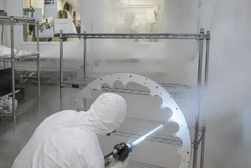 Joe Wallig, a mechanical engineering associate, prepares a metal ring component of the injector gun for installation using a jet of high-purity dry ice in a clean room.