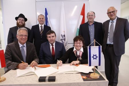 Milton Friedman University President Ferenc Pártos (front row, far left) and Bar-Ilan U. Vice President for Research Prof. Shulamit Michaeli (front row, far right) sign the agreement flanked by Minister of State for Higher Education of Hungary Dr. László Palkovics (front row, center) and (back row left to right): Chief Rabbi of the Unified Hungarian Jewish Congregation Rabbi Slomó Köves, Ambassador of Hungary to Israel Dr. Andor Nagy, BIU Deputy President Prof. Moshe Loewenstein and Research Authority Director Dr. Eli Even