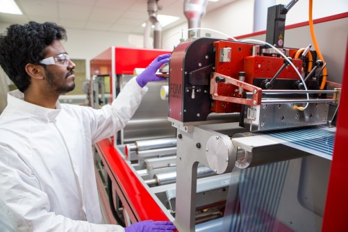UW student working on the roll-to-roll printer at the Washington Clean Energy Testbeds.