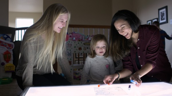 CU Boulder researcher Lameese Akacem, right, and undergraduate research associate Allie Coy work with a preschooler on a light table.