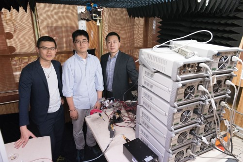 Georgia Tech researchers are shown with electronics equipment and antenna setup used to measure far-field radiated output signal from millimeter wave transmitters. Shown are Graduate Research Assistant Huy Thong Nguyen, Graduate Research Assistant Sensen Li, and Assistant Professor Hua Wang.