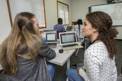 Alyssa Blanton (left) of the University of Texas and Coral Salort of the University of Puerto Rico, Rio Piedras Campus collaborate on a computational physics problem in which they model the decay of radioactive medical tracers.